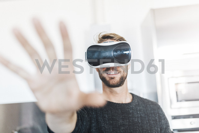 Smiling man wearing Virtual Reality Glasses - GIOF03183