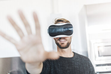 Smiling man wearing Virtual Reality Glasses - GIOF03183