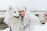 White dressed woman taking selfie with her white dog in winter - ZEDF00838