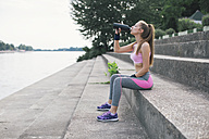 Sporty woman drinking water at the riverbank - MOMF00227
