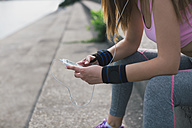 Close-up of sporty woman with cell phone and earphones - MOMF00230
