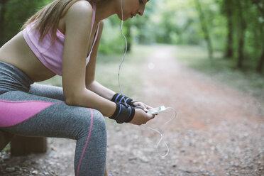 Sporty woman having a break in forest - MOMF00236