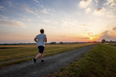 Man running in rural landscape at sunset - PUF00691