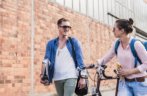 Young couple with bicycle walking and talking - UUF11517