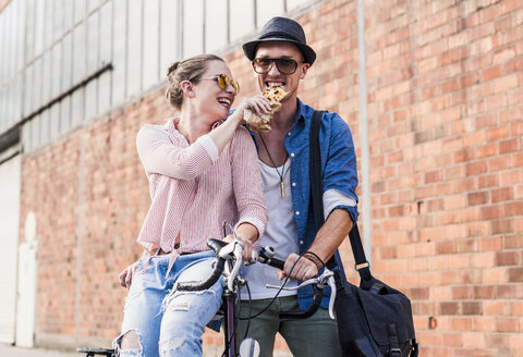 Happy young couple with bicycle sharing a snack - UUF11520