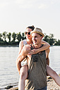 Young man giving girlfriend piggyback ride at the riverbank - UUF11535
