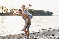 Young man giving girlfriend piggyback ride at the riverbank - UUF11538