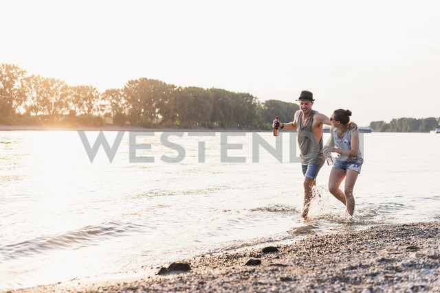 Happy young couple wading in river at sunset - UUF11547