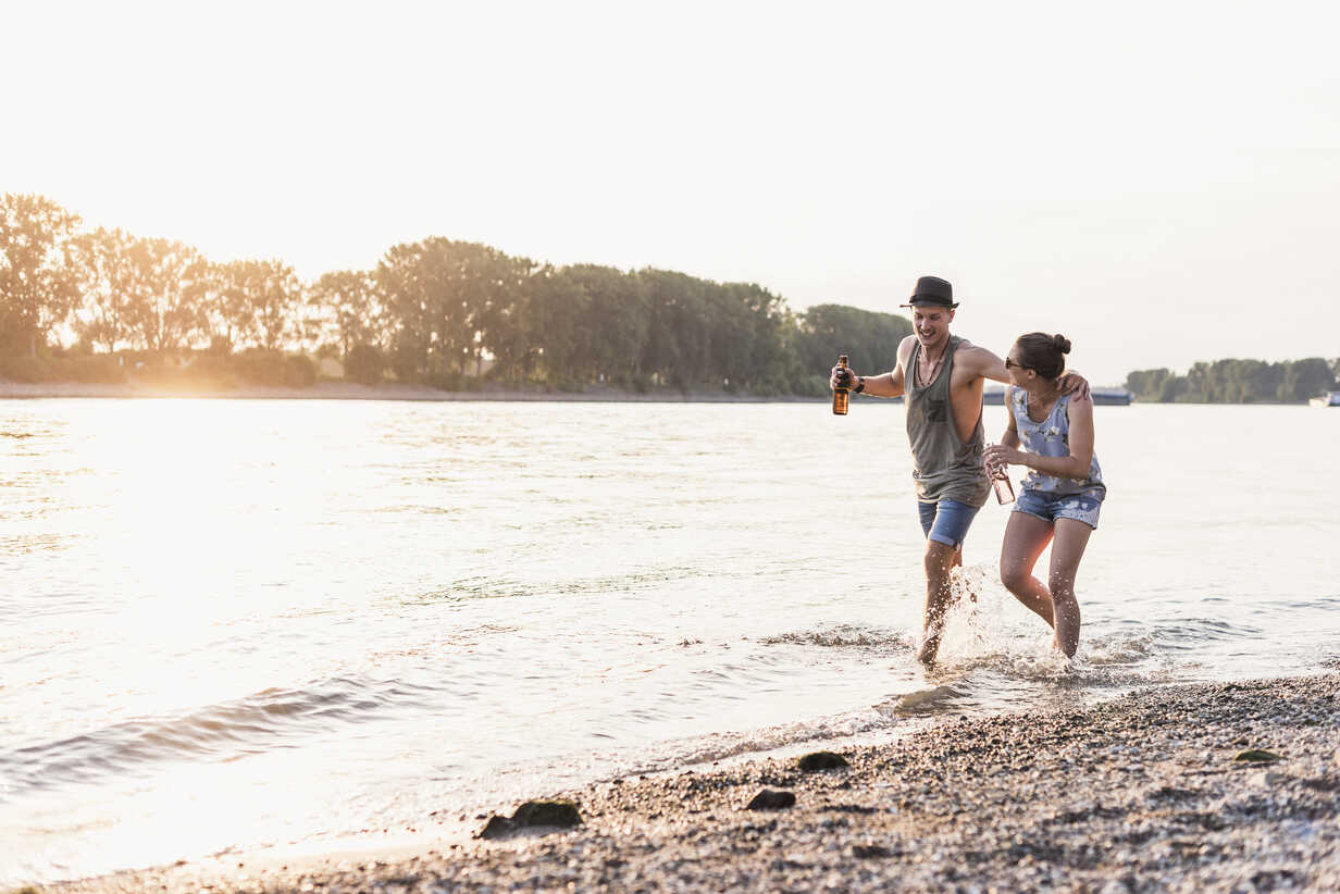 Happy young couple wading in river at sunset - UUF11547 - Uwe Umstätter/Westend61