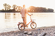 Young man walking with bicycle at the riverbank at sunset - UUF11553