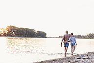 Young couple wading in river at sunset - UUF11556