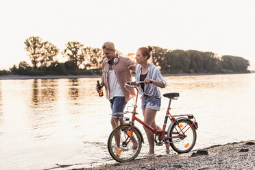 Young couple with bicycle wading in river - UUF11559