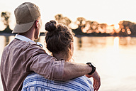 Young couple watching the sunset above a river - UUF11562