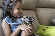 Happy little girl sitting on the couch with puppy on her lap - JASF01798