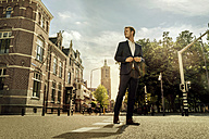 Netherlands, Venlo, businessman standing on a street - KNSF02403