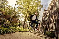 Netherlands, Venlo, businessman jumping on pavement - KNSF02406
