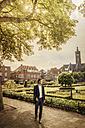 Netherlands, Venlo, businessman standing on pavement - KNSF02409
