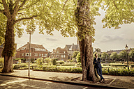 Netherlands, Venlo, businessman leaning against a tree - KNSF02412