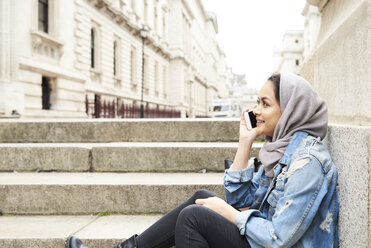 UK, England, London, young woman wearing hijab on cell phone in the city - IGGF00120