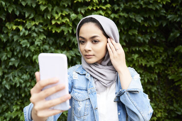 Young woman looking at her phone screen wearing hijab - IGGF00123
