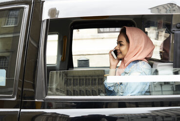 UK, England, London, young woman wearing hijab on the phone in a taxi - IGGF00129