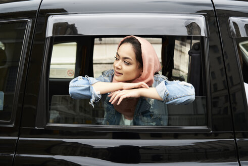 UK, England, London, young woman wearing hijab looking out of a taxi - IGGF00132