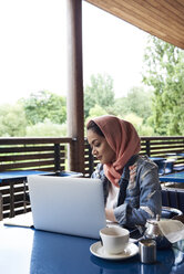 Young woman wearing hijab studying with her laptop on a terrace of a cafe - IGGF00135