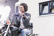 Smiling young woman on her motorcycle - UUF11568