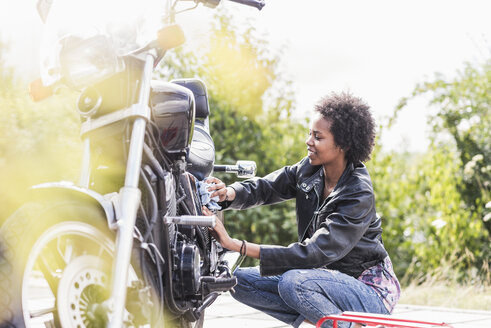 Young woman cleaning her motorcycle - UUF11571