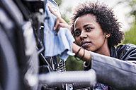 Young woman cleaning her motorcycle - UUF11574