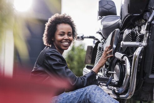Young woman maintaining her motorcycle - UUF11577