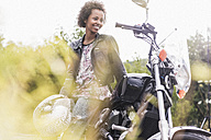 Smiling young woman with her motorcycle - UUF11580