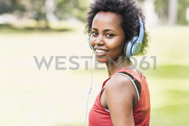 Portrait of smiling sporty young woman with headphones in park - UUF11586