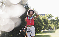 Smiling sporty young woman with bicycle in park - UUF11592