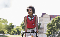 Smiling sporty young woman on bicycle in park - UUF11595