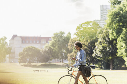 Young woman with cell phone pushing bicycle in park - UUF11604