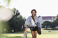 Smiling young woman with cell phone and bicycle in park - UUF11610