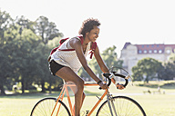 Smiling young woman riding bicycle in park - UUF11619