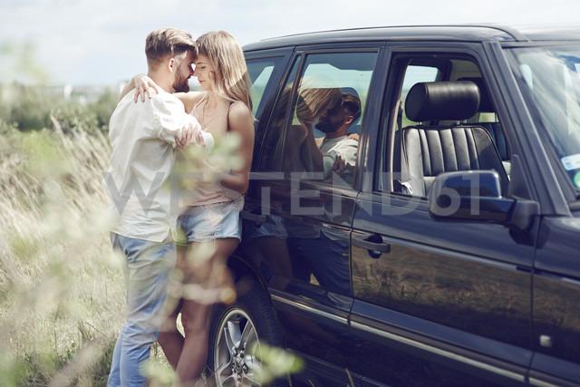 Affectionate young couple outside car - ABIF00009