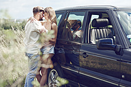 Affectionate young couple outside car - ABIF00009