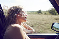 Young woman leaning out of car window - ABIF00012