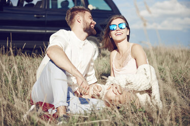 Happy young couple sitting on field next to car - ABIF00018