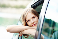 Portrait of young woman leaning out of car window - ABIF00021