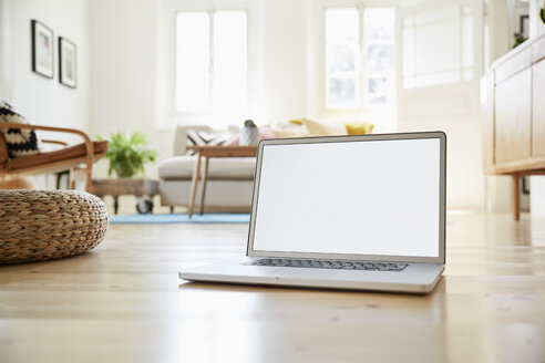 Laptop standing on wooden floor in a bright modern living room of an old country house - PDF01272