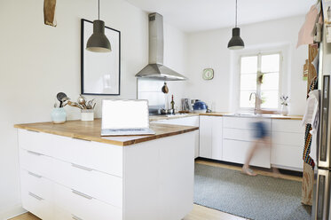 Laptop standing on worktop in a modern kitchen - PDF01275