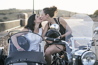 Two women kissing on a sidecar at sunset - JASF01810