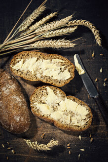 Buttered bread and ear of wheat on dark wood - MAEF12402