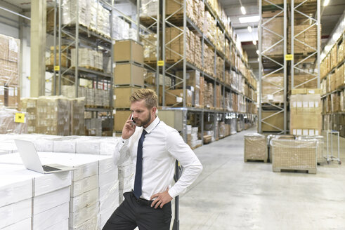 Businessman with laptop and cell phone in warehouse - LYF00761