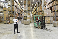 Businessman with laptop in warehouse and worker on forklift - LYF00764