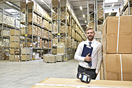 Confident businessman with clipboard and barcode scanner in warehouse - LYF00767